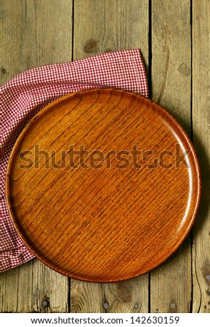 empty wooden plate on the old wooden table - stock photo