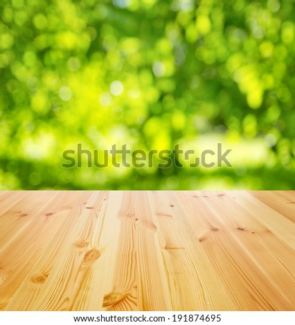 empty wooden table against sunny garden for background - stock photo