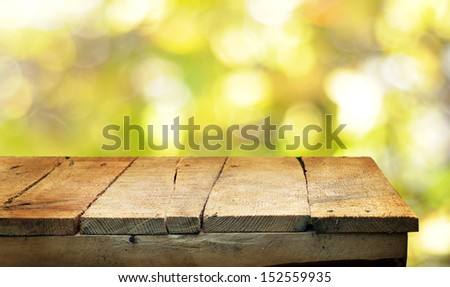 Empty wooden table and autumn background - stock photo