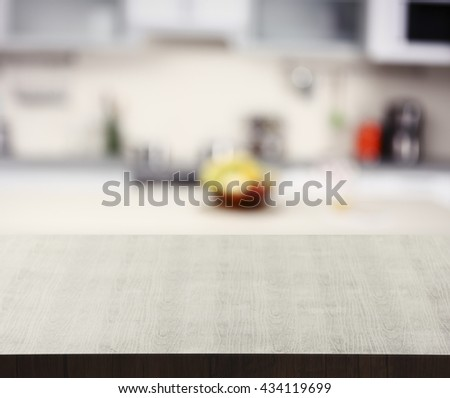 Empty wooden table and blurred kitchen background - stock photo