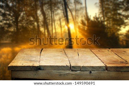 Empty wooden table and defocused autumn dawn in background. Great for product display montages - stock photo