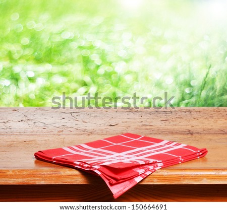 Empty wooden table and fresh green grass in background - stock photo