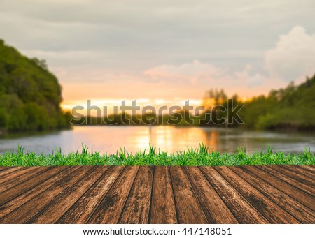Empty wooden table and grass with river and muontain natural bokeh background. Product display template. - stock photo