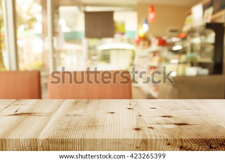 Empty wooden table on coffee shop blur background.