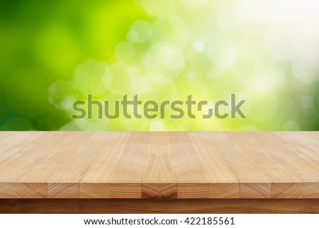 Empty wooden table on natural green background. - stock photo