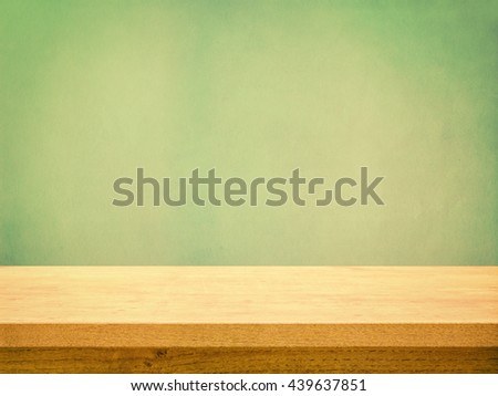 Empty wooden table on pastel green textured wall, retro toned - stock photo