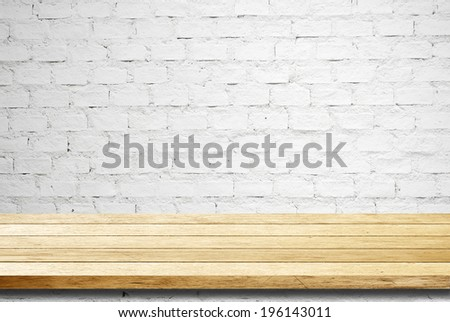 Empty wooden table over white brick wall, template. - stock photo