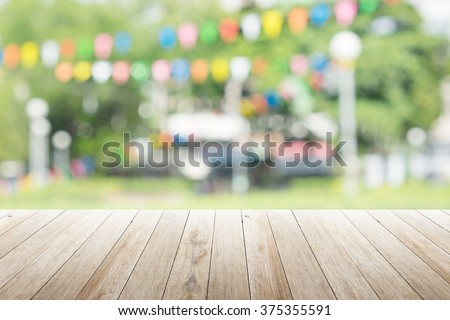 Empty wooden table with blurred party on background,  fun / spring concept - stock photo
