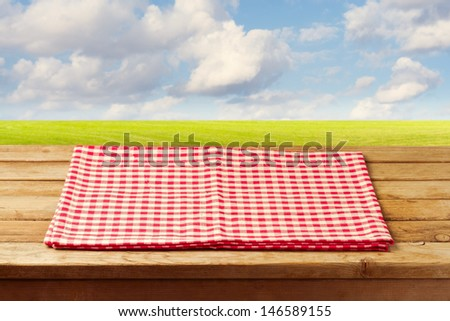 Empty wooden table with red checked tablecloth over beautiful landscape with green meadow and blue sky - stock photo