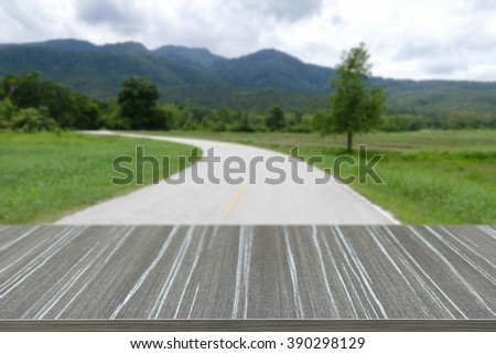 empty wooden table with view of the road and mountain in countryside blur background for displaying your product