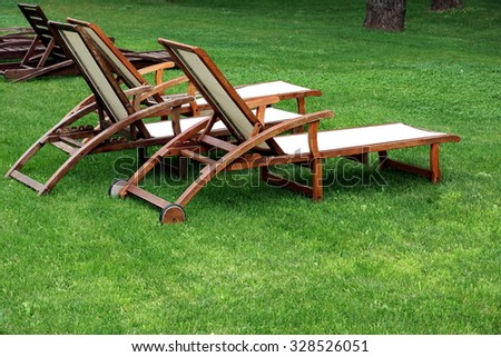 Empty Wooden Weathered Lounger On The Backyard Lawn At The Summertime Evening - stock photo