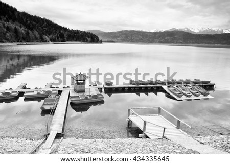 Empty wooden wharf mole. Blue Alps lake with Rental rowing boats in marina. Wharf for trip ships. - stock photo