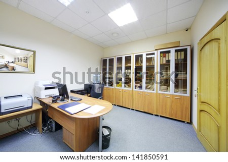 Empty working area with armchair and desktop and bookcase in modern office. - stock photo