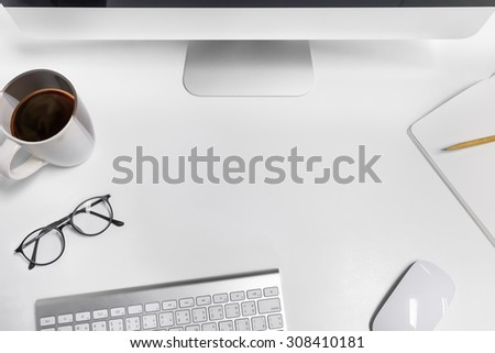 Empty workspace on white table. View from above on the clean, well organized working space framed by PC, keyboard, mouse, pencil, coffee cup and glasses - stock photo