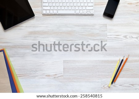 Empty workspace on wooden table. View from above on the clean, well organized working space framed by tablet PC, keyboard, cell phone, colored booklets and pencils. - stock photo