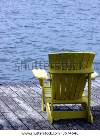 Empty yellow Adirondack chair on a dock over the water - stock photo