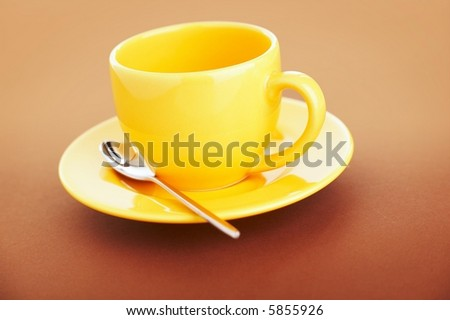 Empty yellow coffee cup over a brown background