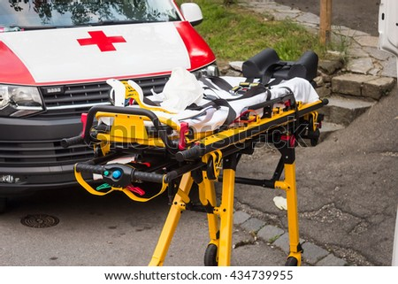 Empty yellow gurney near ambulance, ready for emergency - stock photo