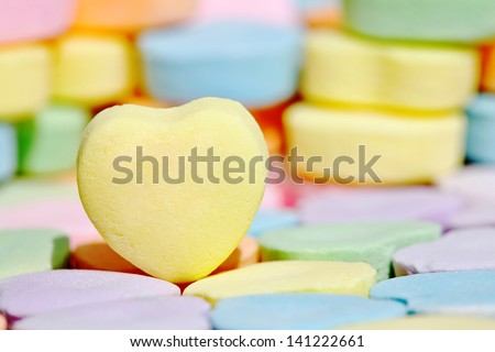 Empty yellow heart candy over colorful bonbon - stock photo