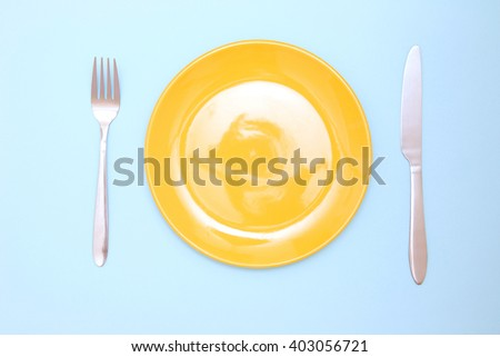 Empty yellow plate, fork and knife on blue background