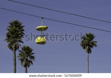 Empty yellow ropeway surrounded by palms - stock photo