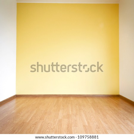 Empty yellow wall and wooden floor room - stock photo
