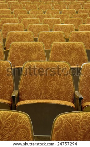 empty yellow wooden cinema/theater seats - stock photo