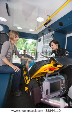 EMT professional caring for a senior woman in an ambulance, caregiver at side - stock photo