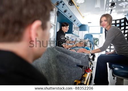 EMT professionals caring for an elderly patient with caregiver at side. - stock photo