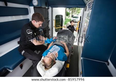 EMT worker feeling pulse in wrist of senior patient - stock photo