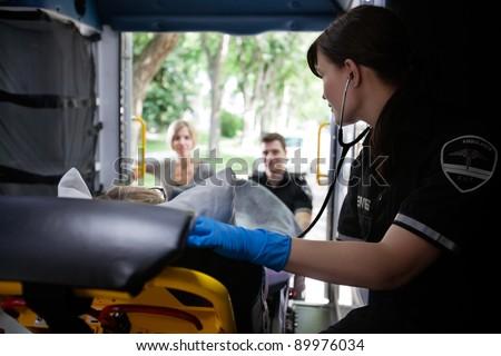 EMT worker listening to heart of elderly patient - stock photo