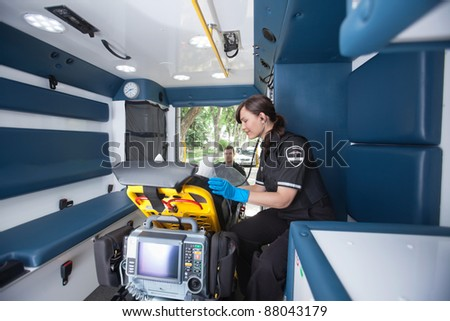 EMT worker listening to heart rate of patient - stock photo