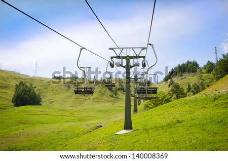 Emtpy chairlift in ski resort. Shot in summer with green grass and no snow - stock photo
