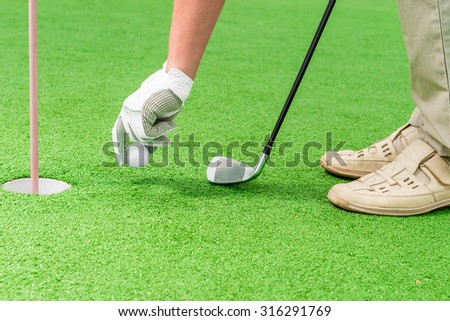en's hand in a glove putting a golf ball near the hole - stock photo