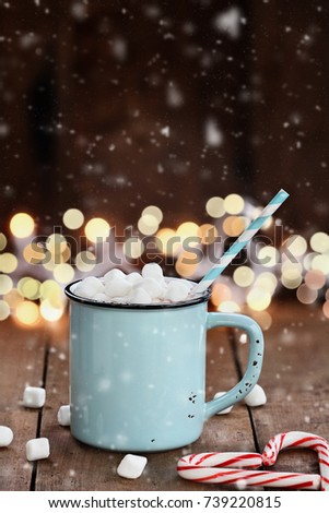 Enamel cup of hot cocoa with mini marshmallows and candy canes with pine boughs and gray scarf against a rustic background with beautiful Christmas lights of bokeh with falling Snow.