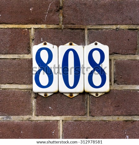 Enameled house number eight hundred and eight, on three separate plates. - stock photo