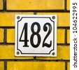 enameled house number four hundred and eighty-two on a yellow brick wall - stock photo