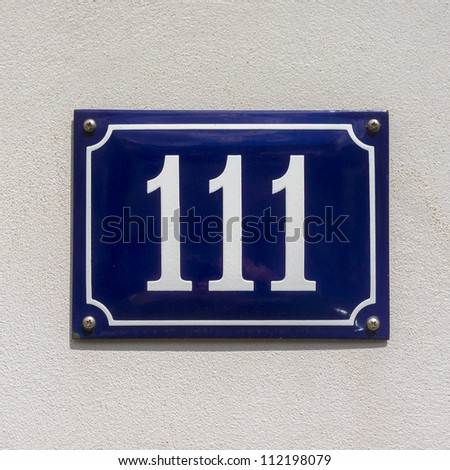 enameled house number one hundred and eleven. White lettering on a blue background - stock photo