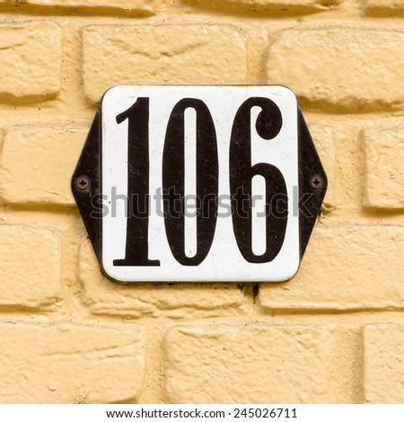 Enameled house number one hundred and six. - stock photo