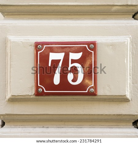 enameled house number seventy five. White numerals on a red background - stock photo