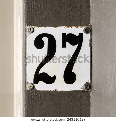 Enameled house number twenty seven. - stock photo