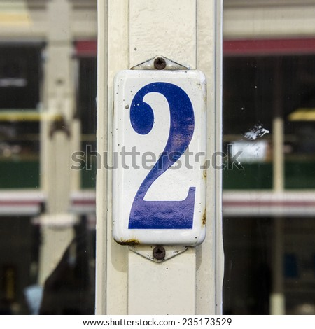 Enameled house number two. Blue numeral on a white background. - stock photo