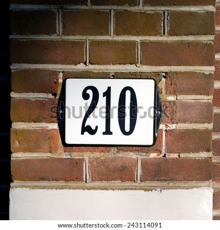 Enameled house number two hundred and ten. Black lettering on a white background. - stock photo