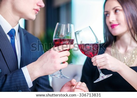 Enamored a festive dinner for two. Romantic dinner in the restaurant. Young loving couple visits a restaurant and raised their glasses of wine close-up view