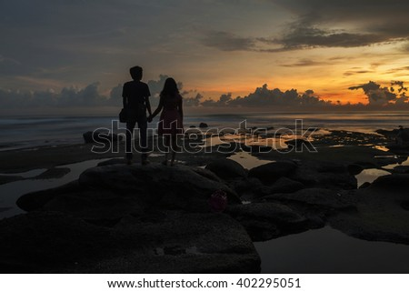 Enamored couple watching a beautiful sunset at beach in Kuta, Bali, Indonesia. - stock photo
