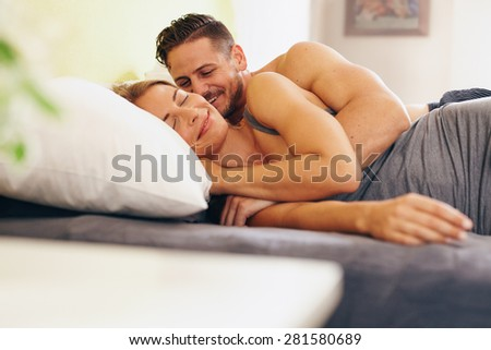 Enamored young couple lying on bed together in the bedroom. Happy man and woman waking up in morning.