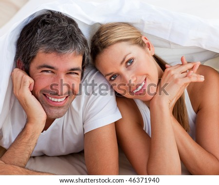 Enamoured couple having fun lying on bed at home - stock photo