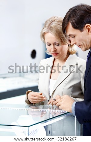 Enamoured couple of middle age at a shop show-window - stock photo