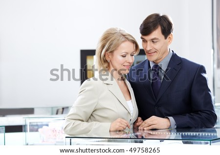 Enamoured couple of middle age in jeweller shop - stock photo