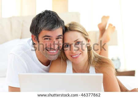 Enamoured couple using a laptop lying on bed at home - stock photo